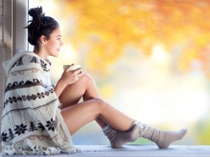 Beautiful young smiling brunette woman with cup of coffee wearing knitted nordic print poncho sitting home by the window.. Blurred fall garden background.
